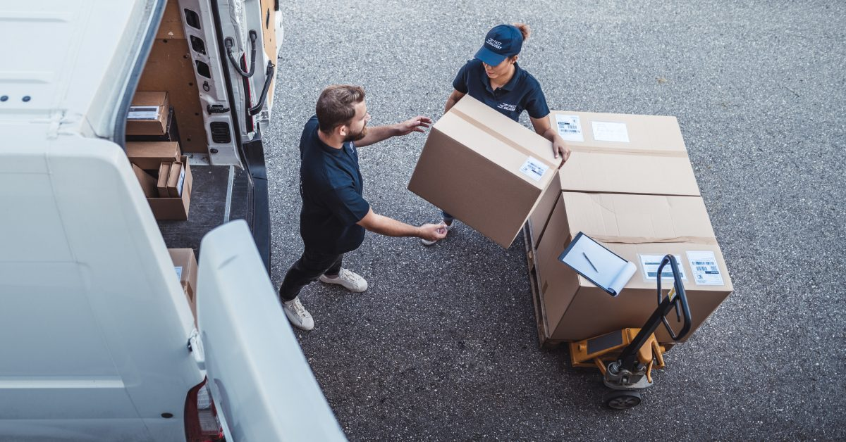 Delivery workers using a Hydraulic Hand Pallet Truck to load a delivery van.