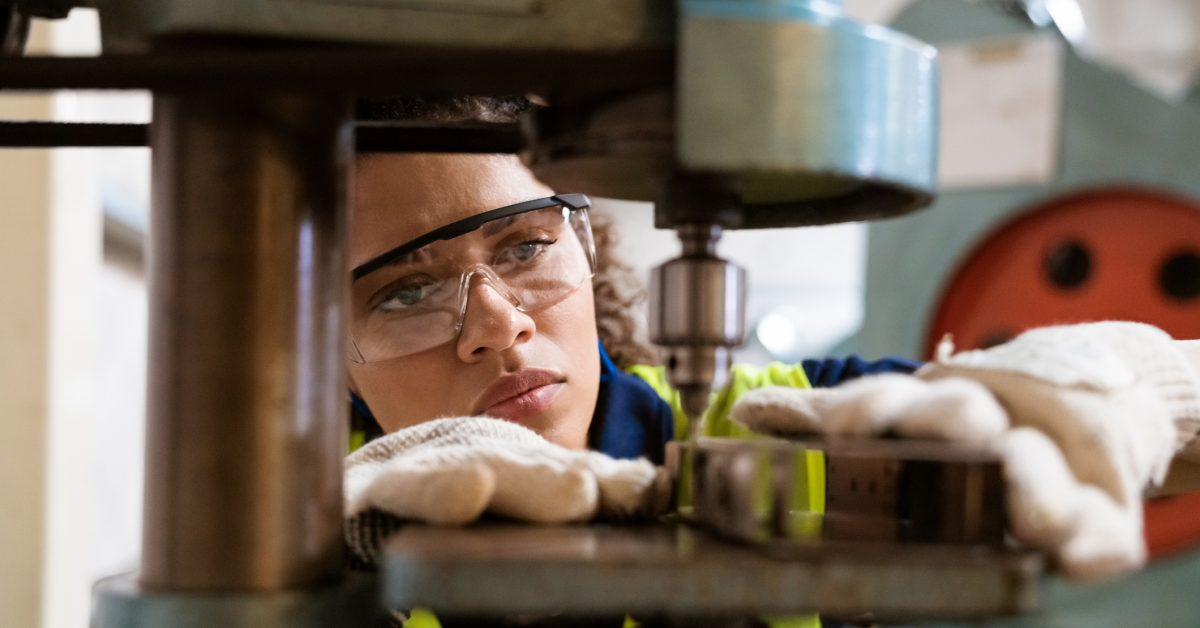 Close-up of female apprentice using yoke machine. Female engineer is wearing protective glasses in factory. She is working in manufacturing industry.
